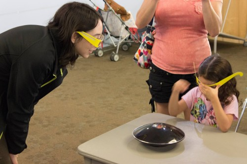 "CIAN graduate student Jasmine amazes this young visitor with the ""holographic"" pig"